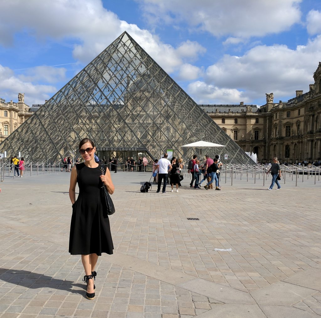 Louvre courtyard glass pyramid woman Paris