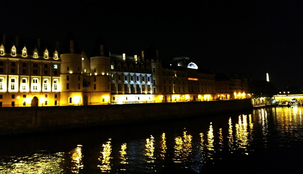 Seine night Conciergerie lights reflected on water