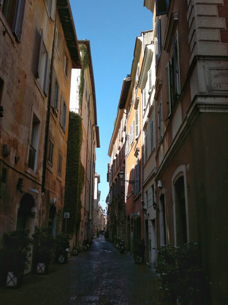 narrow cobblestone street Rome stone buildings shutters blue sky