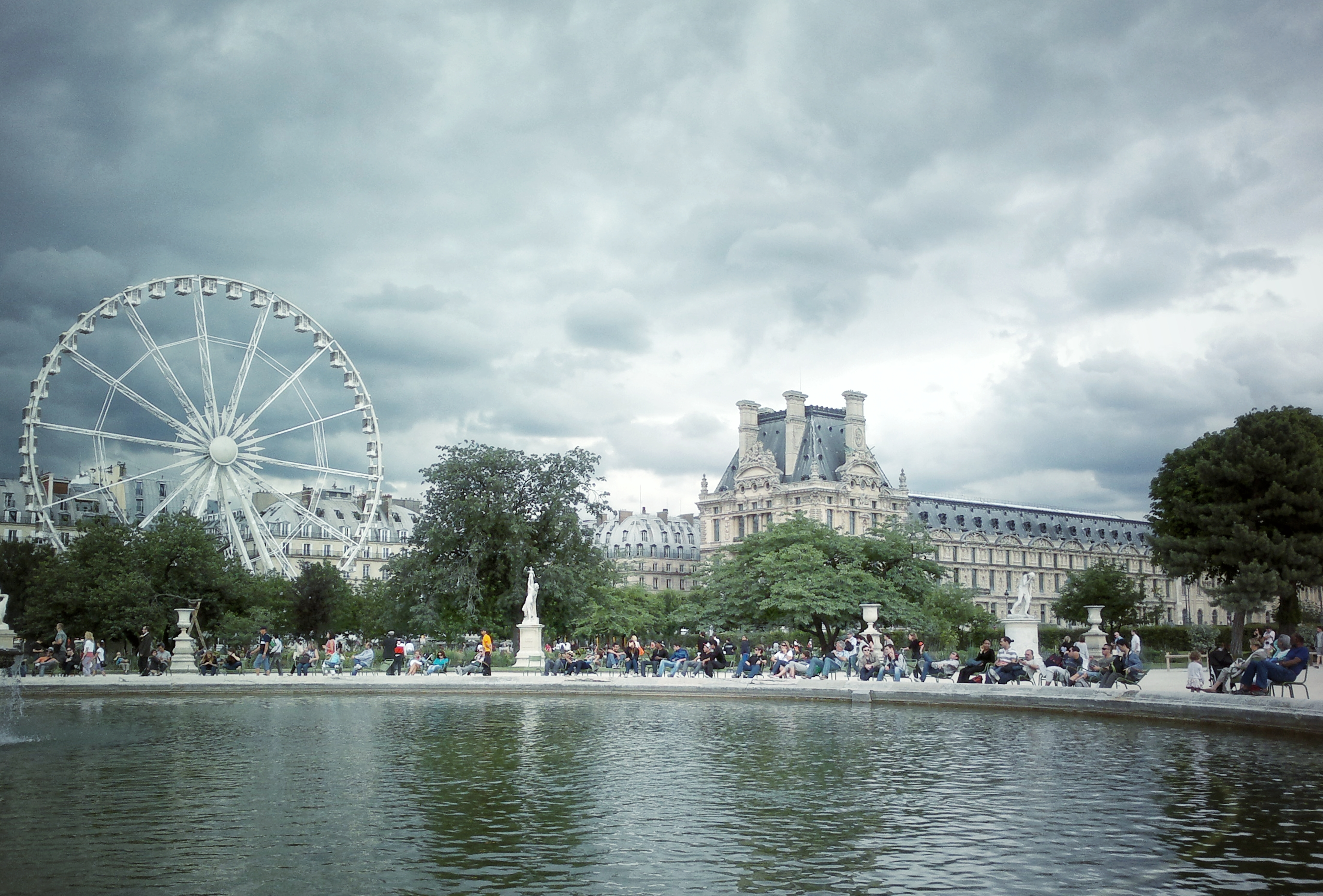 fountain Ferris wheel Louvre museum cloudy sky