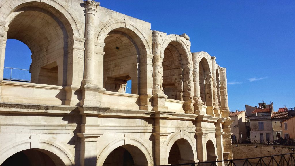 exterior Roman Arles amphitheatre arches blue sky stone buildings