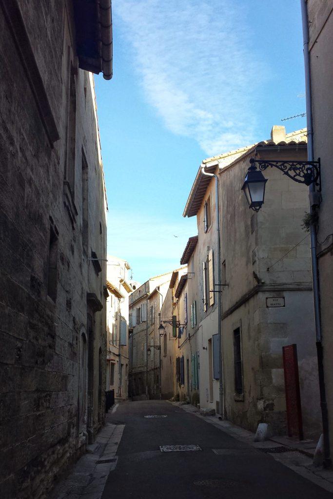 lane stone buildings shutters street lamp blue sky Arles