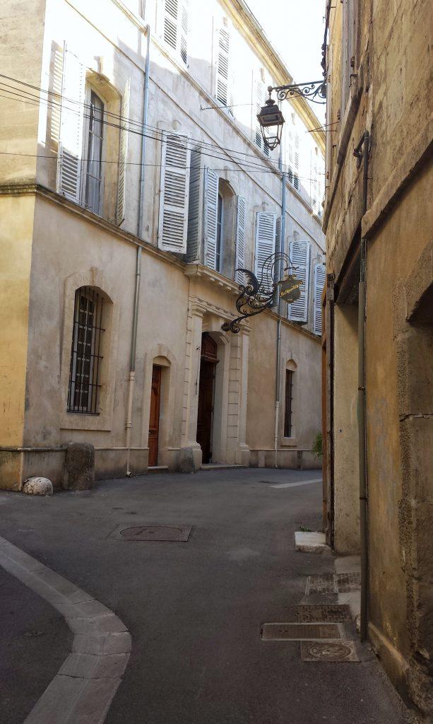curved lane stone buildings blue shutters street lamp Arles