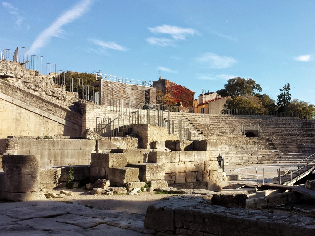 Roman Theatre Arles stone fragments seating stage blue sky clouds trees