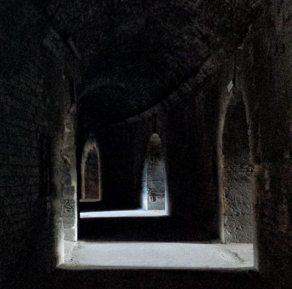 Roman Arles Amphitheatre dark tunnel arches strong light shadow