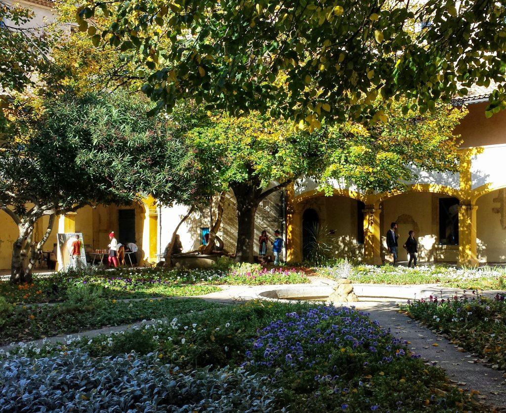 interior courtyard yellow arches tree shadow flowers L'espace Van Gogh Arles