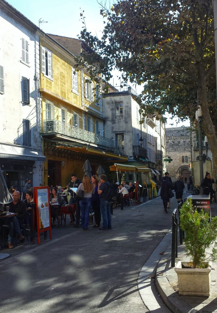 village square outdoor cafes tree shadows Arles