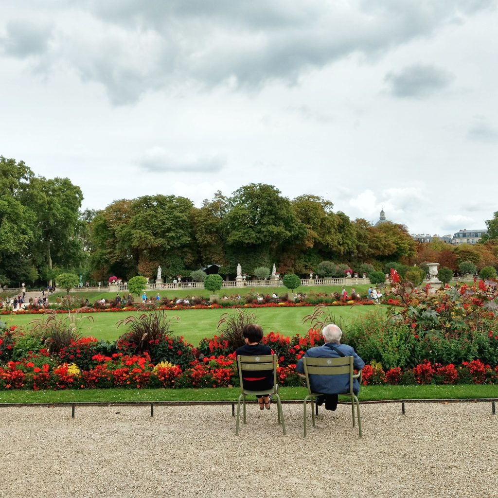 park grass flowers elderly couple on chairs Jardin du Luxembourg