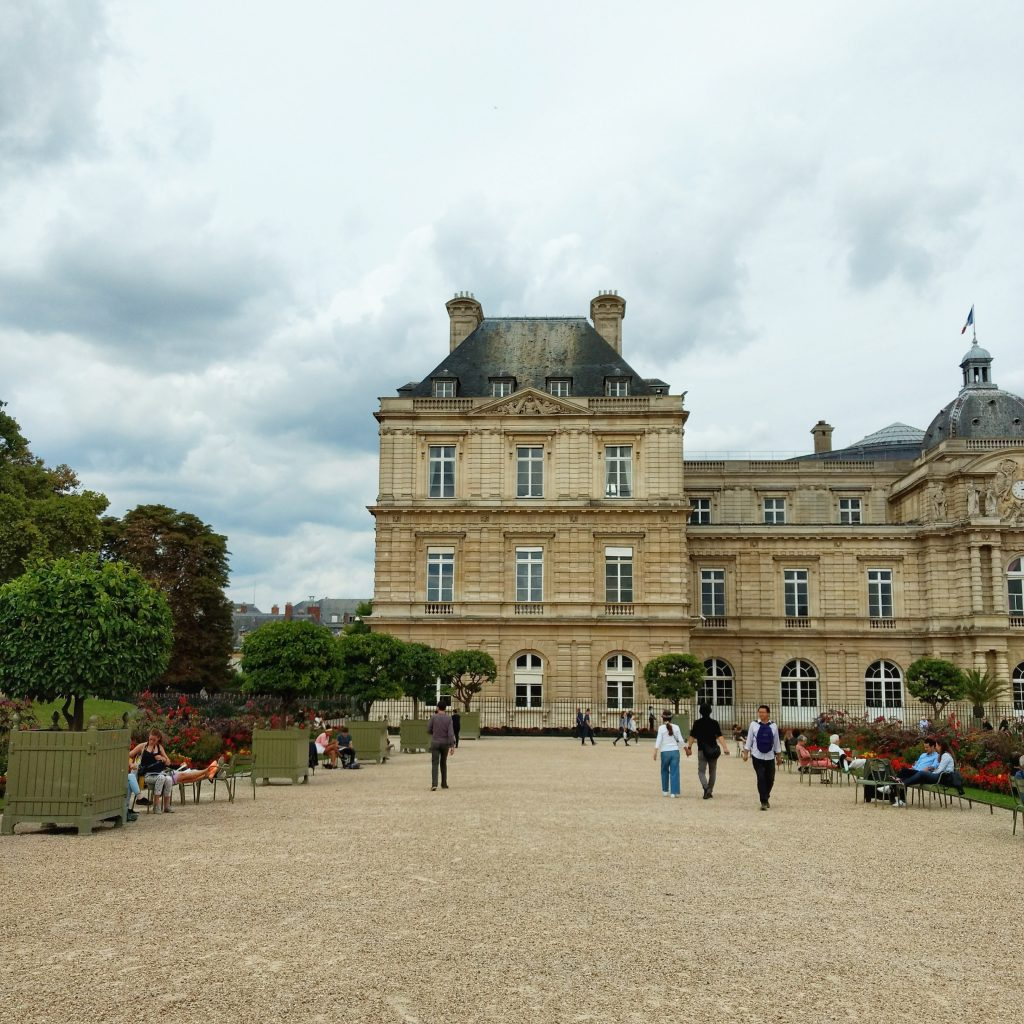 park gravel path people walking old building clouds Jardin du Luxembourg