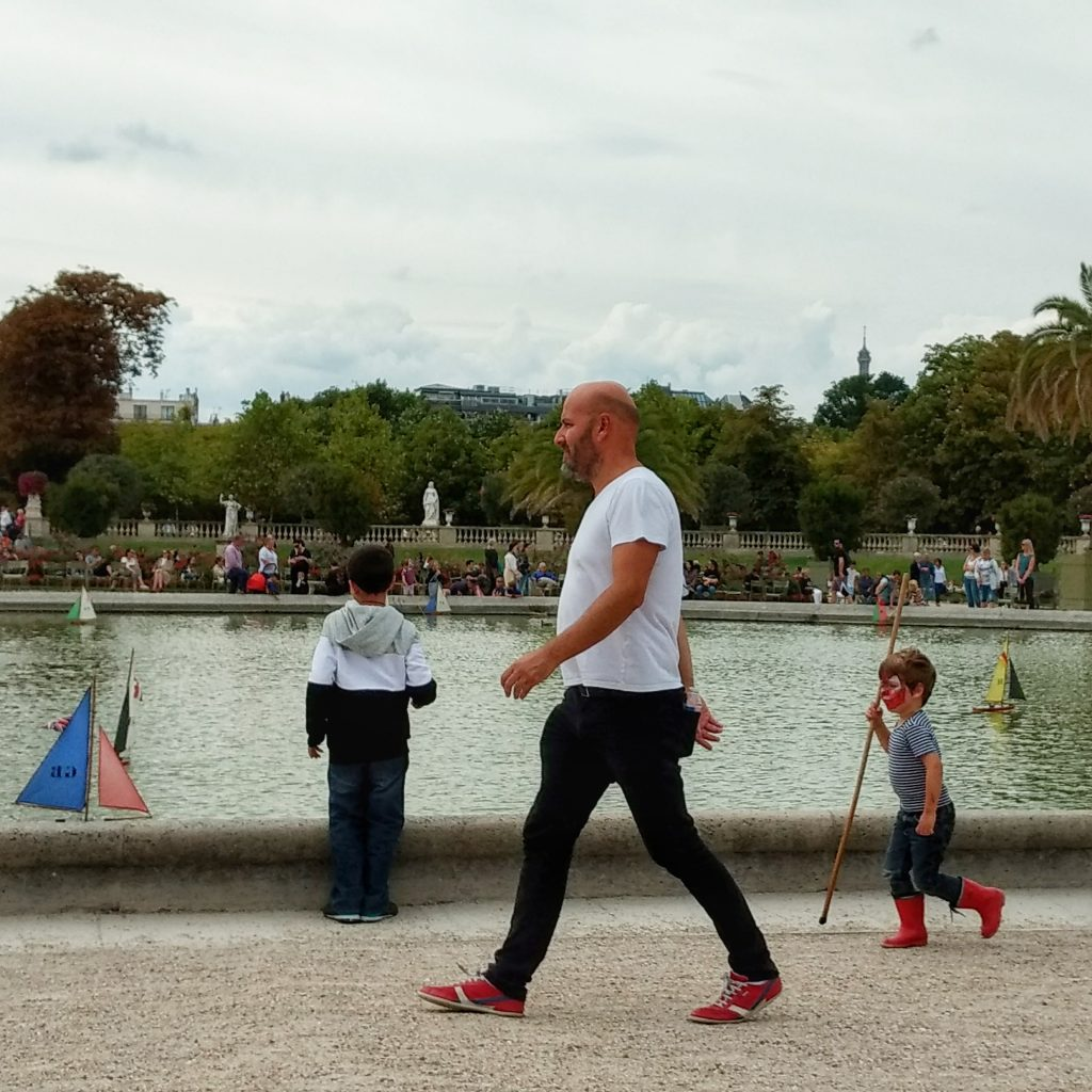 park pond toy boats children boy in red galoshes Jardin du Luxembourg