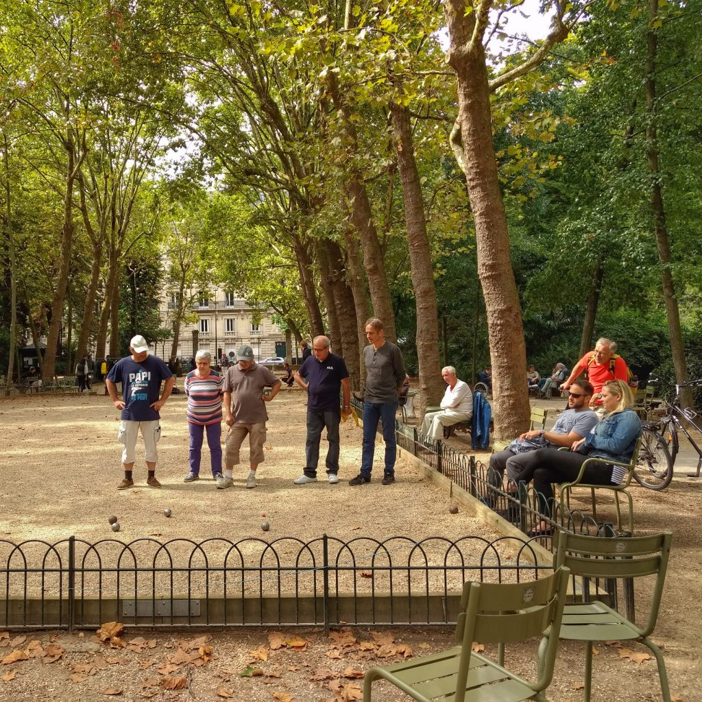 park older people playing petanque onlookers trees Jardin du Luxembourg