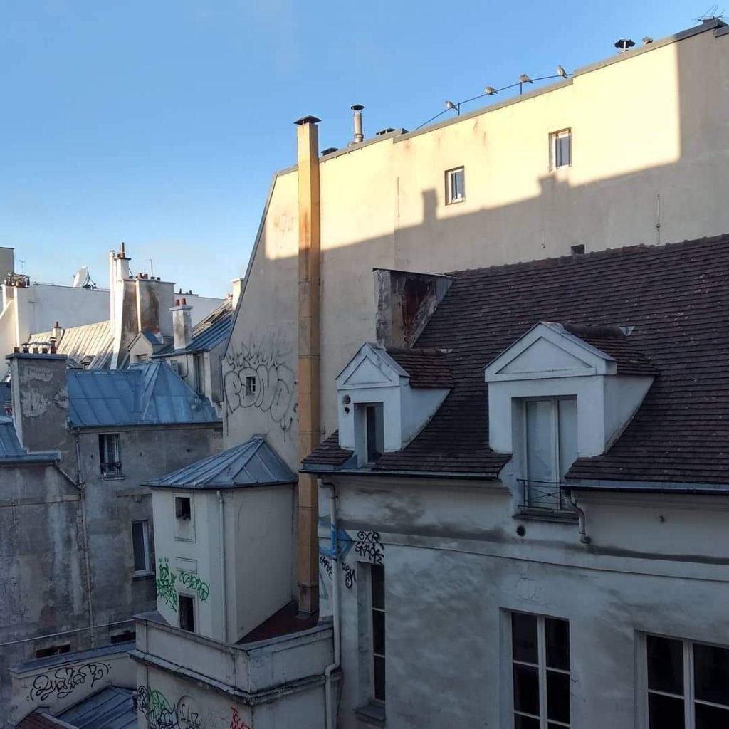 view from a top story window building across street morning light blue sky Haut Marais, Paris