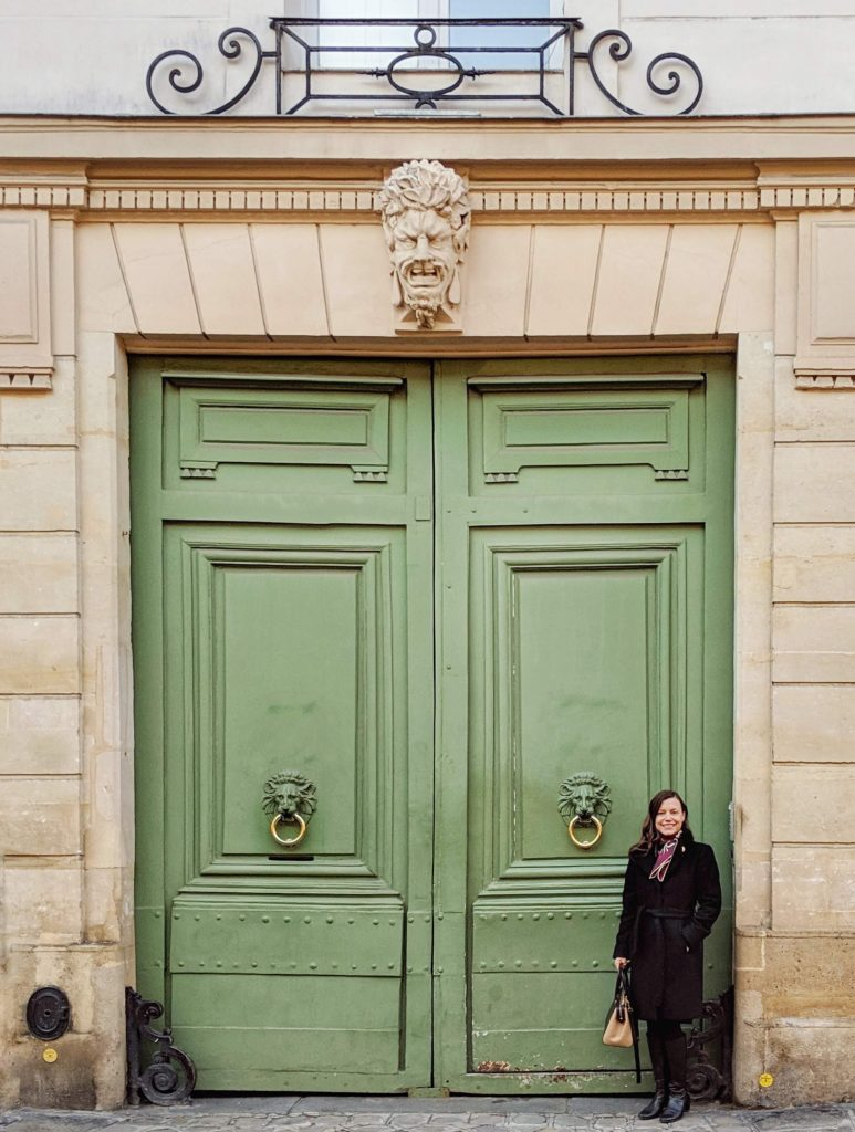 woman standing in front of large green doors with lion's head door knockers Paris