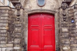 red door in stone facade Parisfa