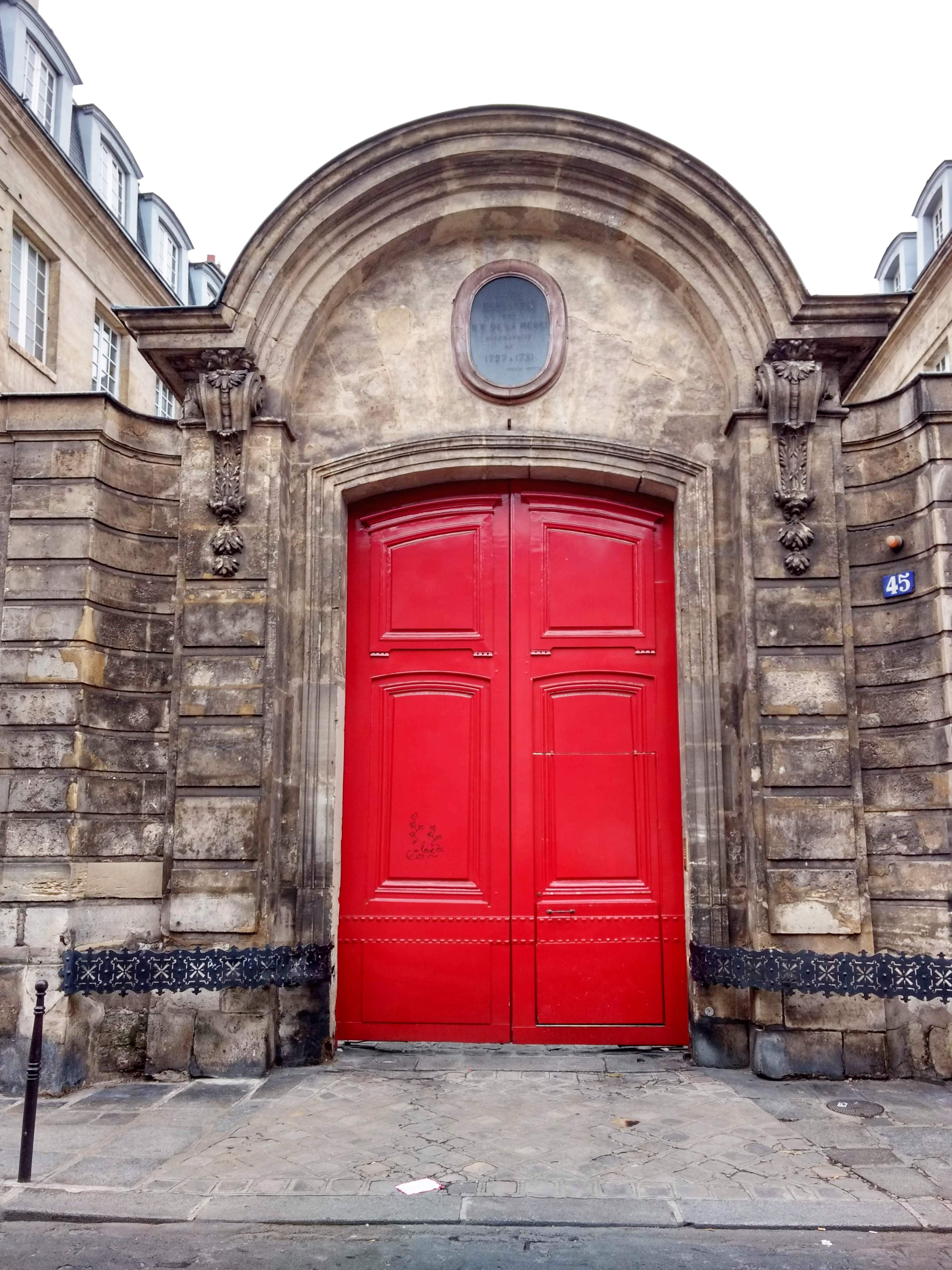 red door in stone facade Paris