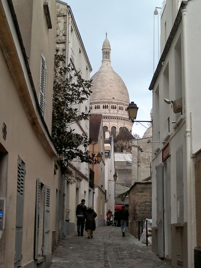 cobbled street looking toward Sacre Coeur church dome Paris