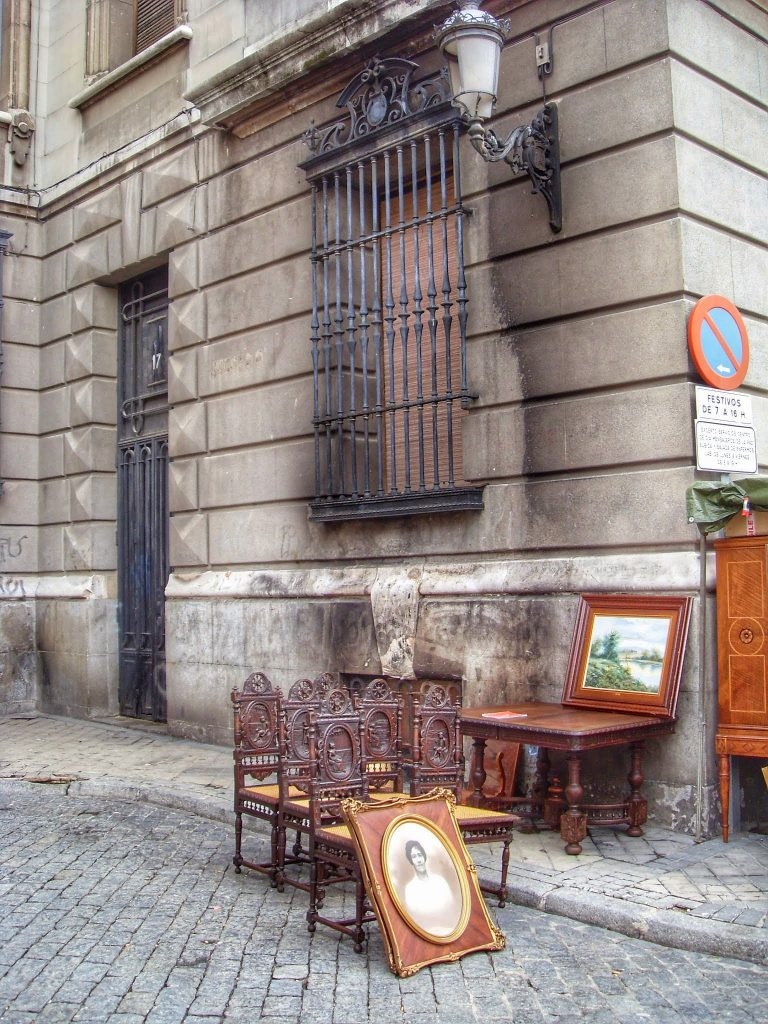 outdoor flea market stone buildings cobble stones antiques on the street wooden chairs paintings