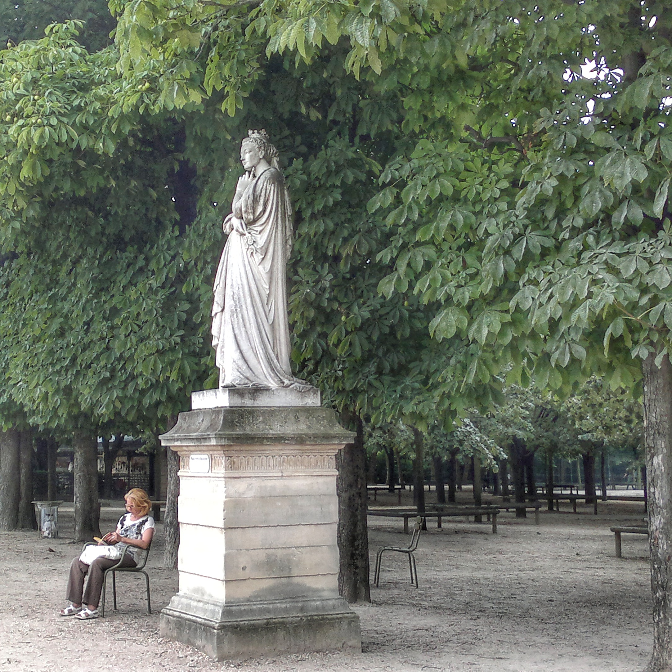 woman in garden reading under trees statue of a queen