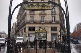 Art Nouveau Paris Metro sign, rainy pavement, stone building in background