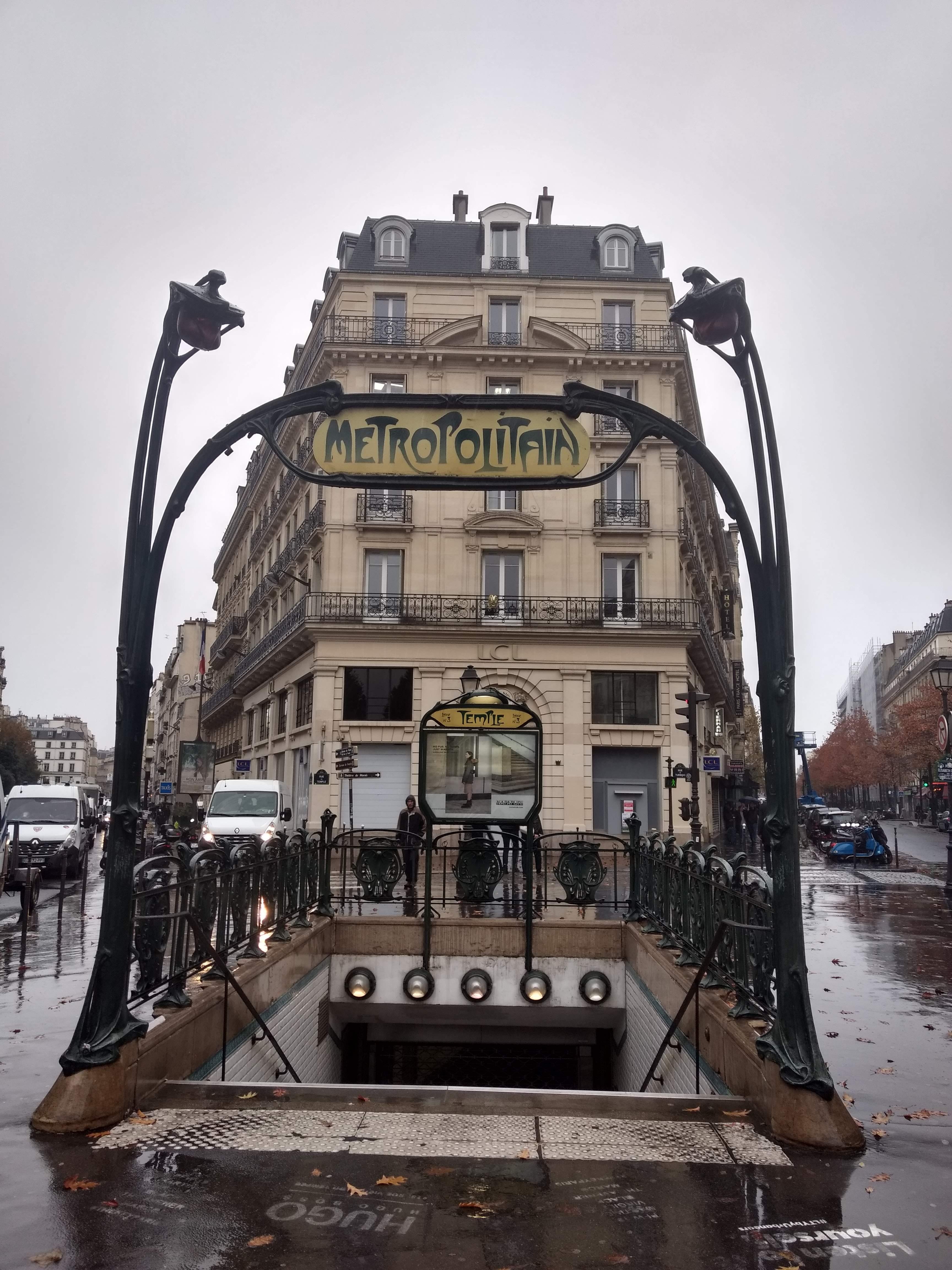 Art Nouveau Paris Metro sign, rainy pavement, stone building in background