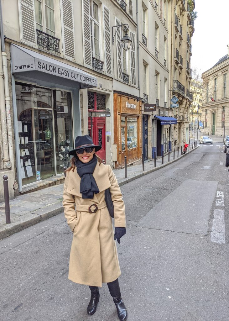 woman smiling in Paris street dressed in coat hat sunglasses