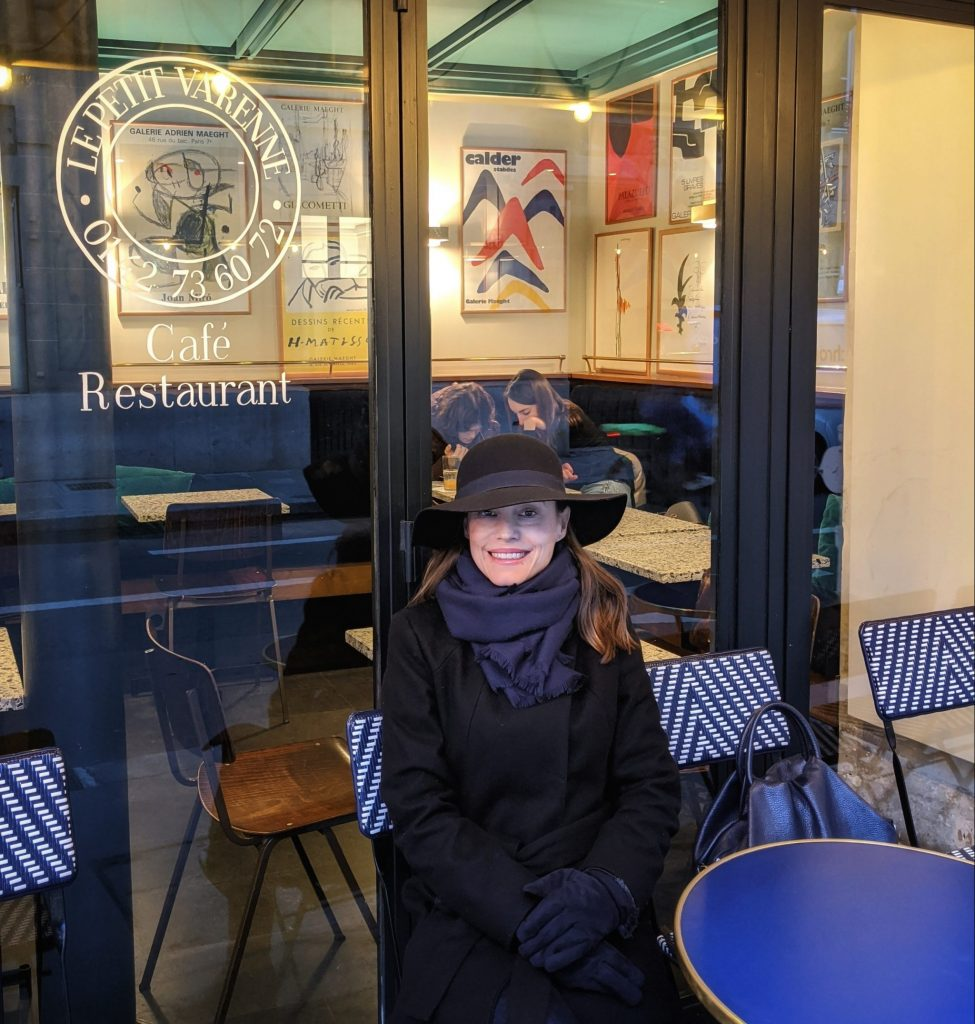 woman in hat and winter coat sitting at outdoor cafe rue de Varenne Paris