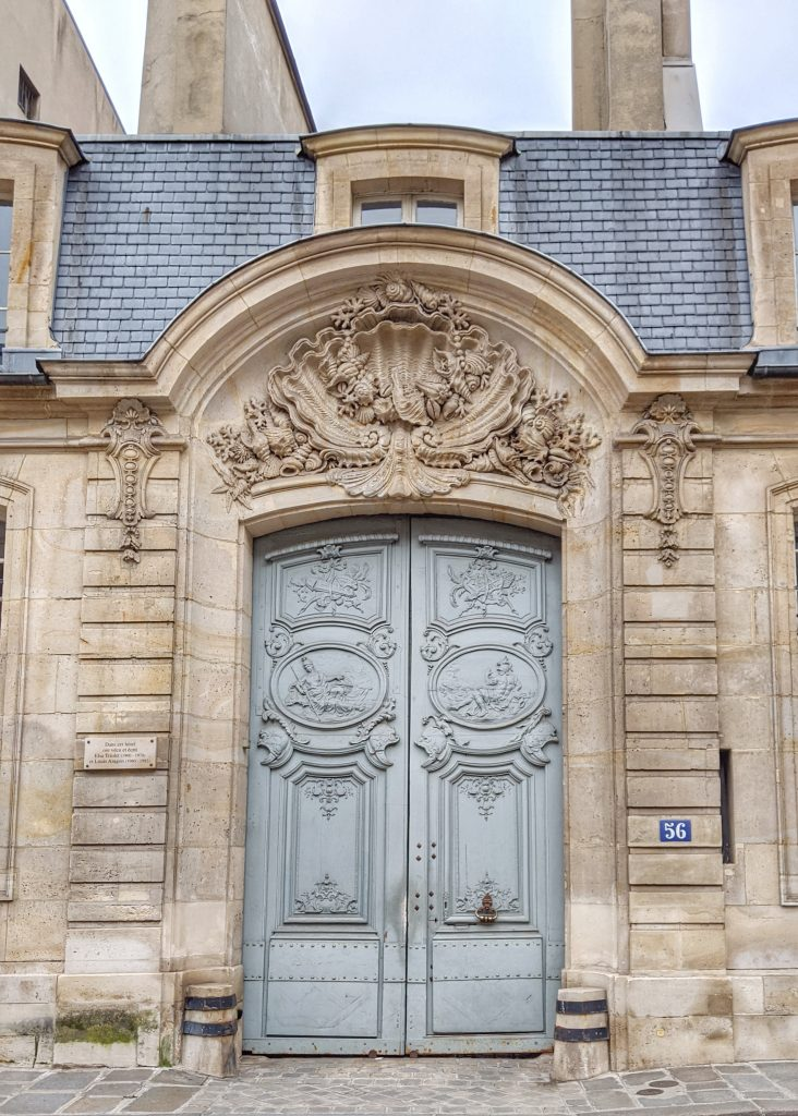 ornate light blue-gray doors in stone portico Paris