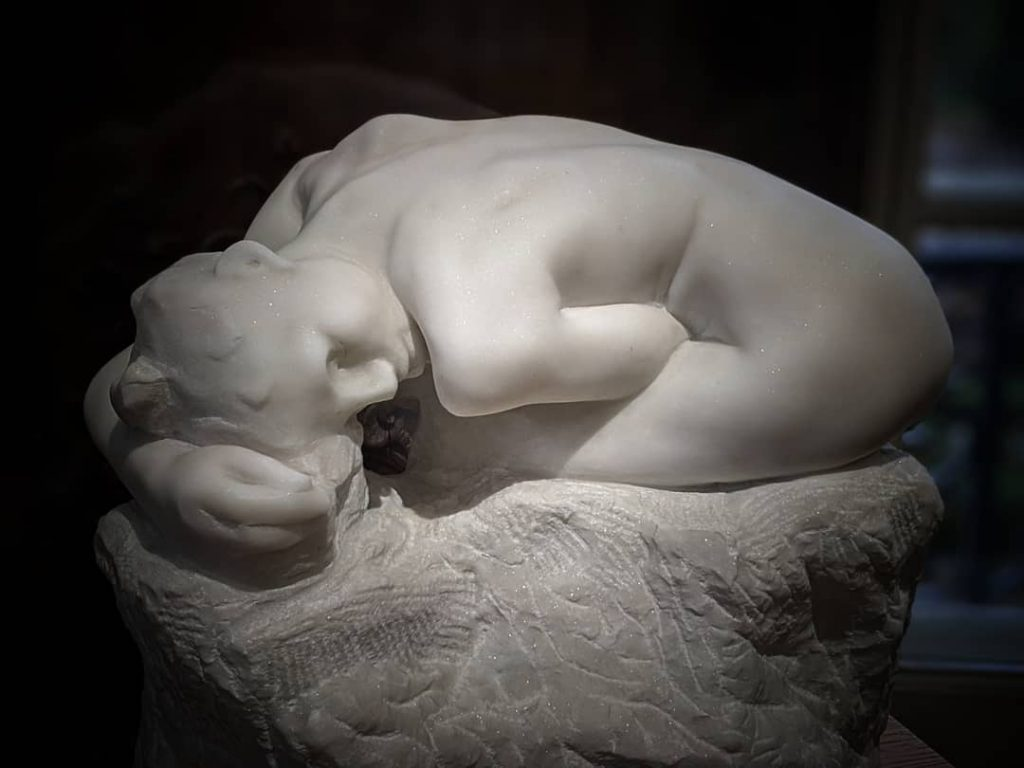 white marble sculpture of a woman folded over